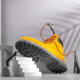Schoenconcept, gele laarzen op de trap, vrouwenbenen en -handen, palmtint op grijze achtergrond, boog en andere geometrische vormen, kleur 2021