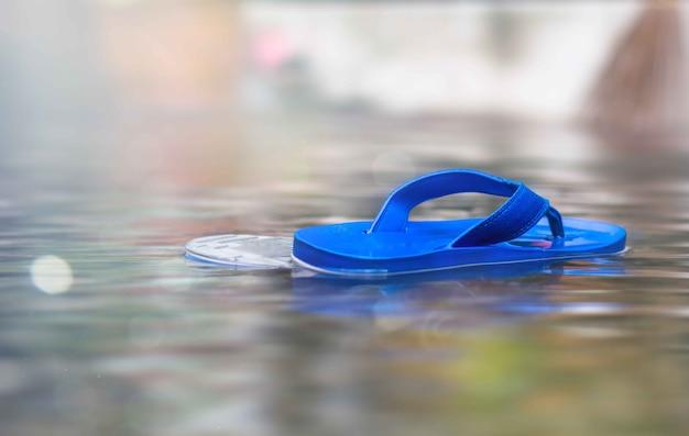Schoenen drijvend op overstroomde straat en na de regen.
