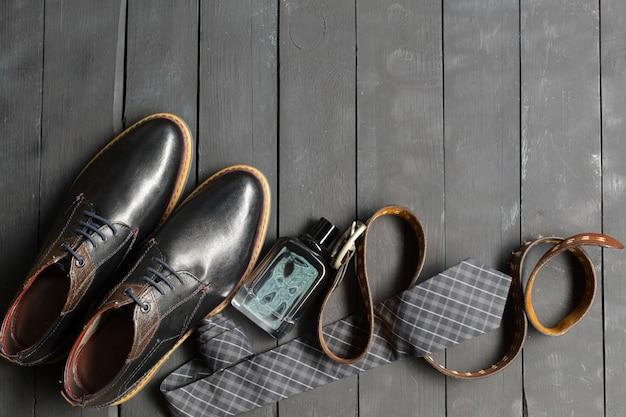 Schoenen en accessoires voor mannen liggen op de houten vloer