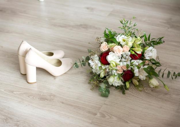 Schoenen en bruidsboeket staan op een lichte ondergrond