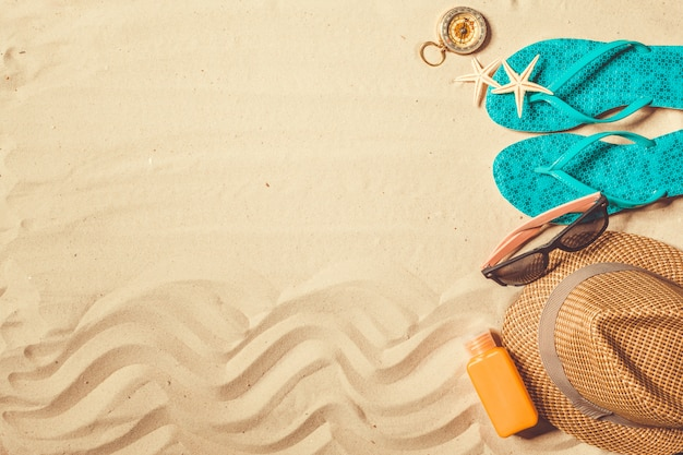 Schoenen en hoed op het strand