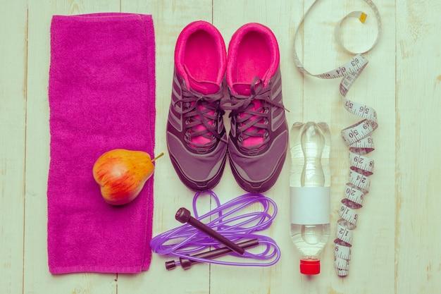 Schoenen en sportartikelen op houten vloer, bovenaanzicht