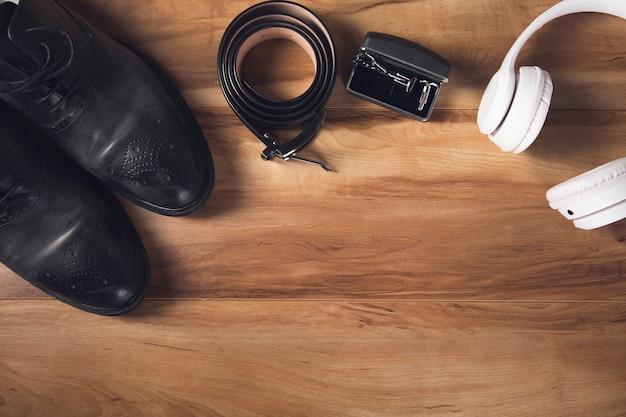 Schoenen met riem en oortelefoon op houten