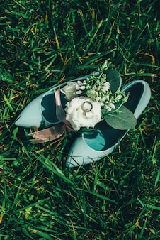 Schoenen met witte bloemen en ringen op het gras