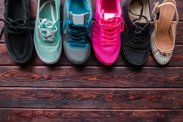 Schoenen van verschillende stijlen op de houten achtergrond