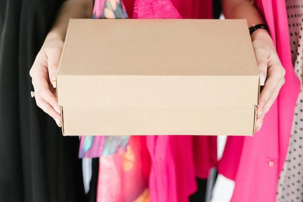 Schoenendoos. mode winkelen levensstijl en trendy accessoires concept. vrouw handen met een kartonnen doos.