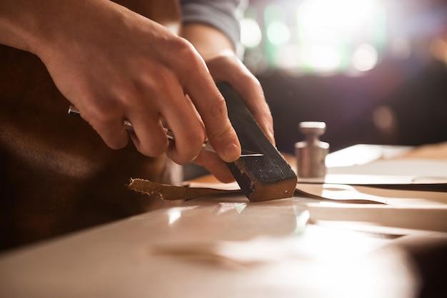 Schoenmaker die een mes scherpt