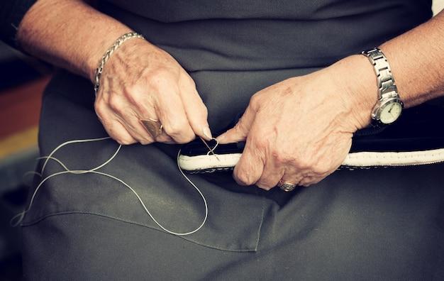 Schoenmaker naait schoenen