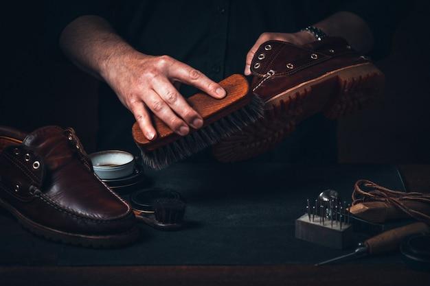 Schoenmaker schoenen schoonmaken met een borstel in zijn atelier