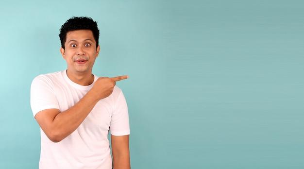 Schok en verrassing gezicht van aziatische man wijs op lege ruimte op een blauwe muur met kopie ruimte.