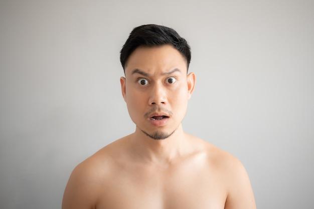 Schok en verrassingsgezicht van de aziatische die mens in topless portret op grijze achtergrond wordt geïsoleerd