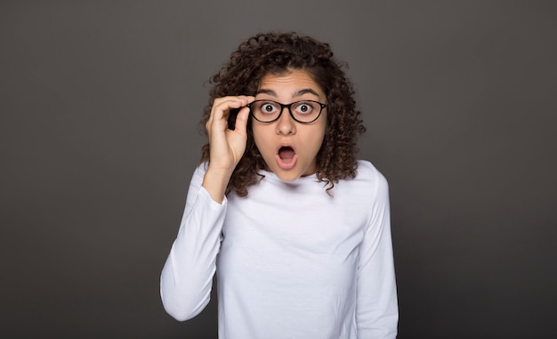Schok op het gezicht van het meisje met een bril. gekke verrassing in een jonge vrouw op een zwarte.