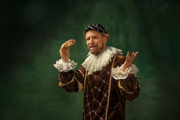 Schokkend eten. portret van middeleeuwse jongeman in vintage kleding met houten frame op donkere achtergrond. mannelijk model als hertog, prins, koninklijk persoon. concept vergelijking van moderne tijdperken, mode.
