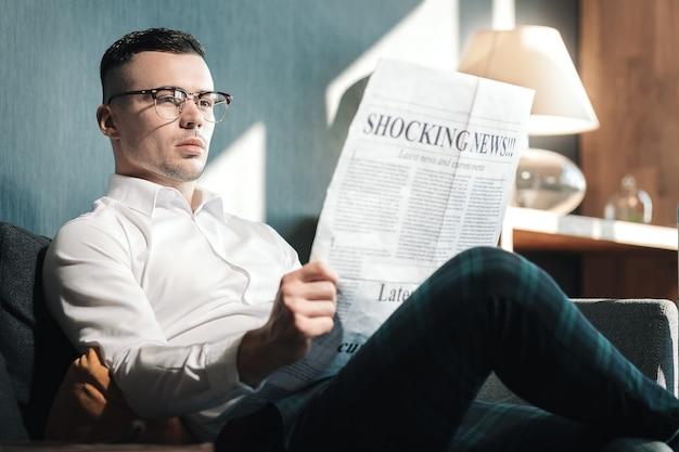 Schokkend nieuws. jonge knappe man met bril schokkend nieuws lezen in zijn hotelkamer