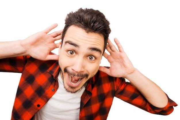Schokkend nieuws. portret van een verraste jonge man in een shirt die lacht terwijl hij tegen een witte achtergrond staat