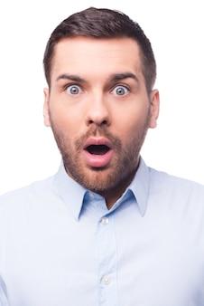 Schokkend nieuws. portret van een verraste jonge man in shirt die naar de camera staart terwijl hij tegen een witte achtergrond staat