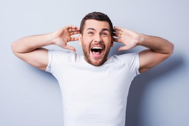 Schokkend nieuws. verrast jonge man die positiviteit uitdrukt en gebaren maakt terwijl hij tegen een grijze achtergrond staat