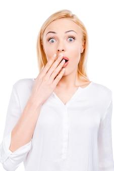 Schokkend nieuws. verrast volwassen vrouw die haar mond met de hand bedekt en naar de camera staart terwijl ze tegen een witte achtergrond staat
