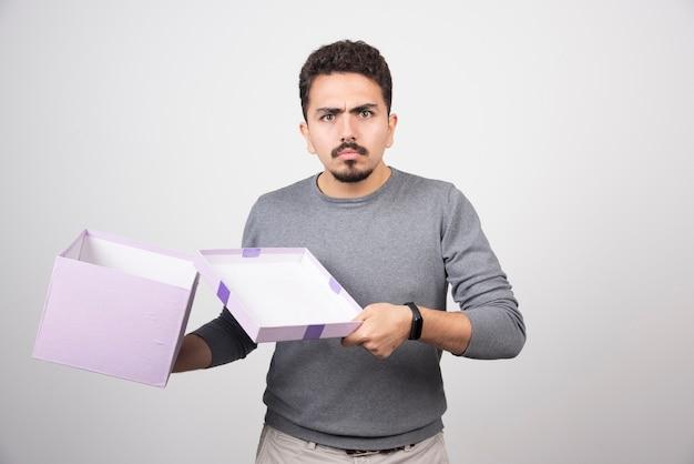 Schokkende man die een paarse doos opent over een witte muur.