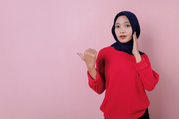 Schokkende mooie jonge vrouw met de duim die rode t-shirt draagt
