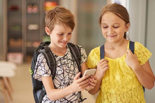 Scholieren die mobiele telefoon gebruiken