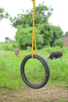 Schommel gemaakt door band en touw op boom op groen veld