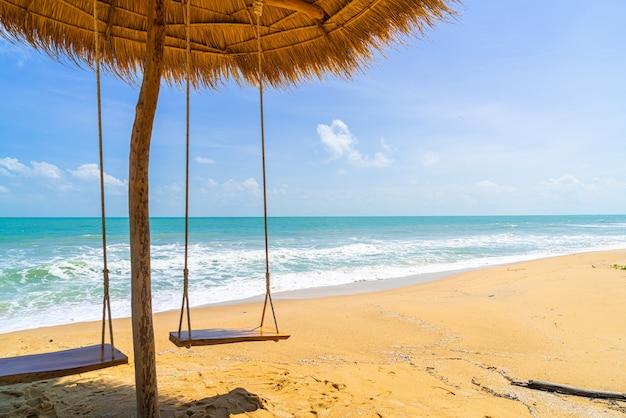 Schommel op het strand met oceaanzee en blauwe lucht
