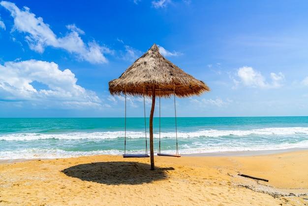 Schommel op strand met oceaan, zee en blauwe hemelachtergrond