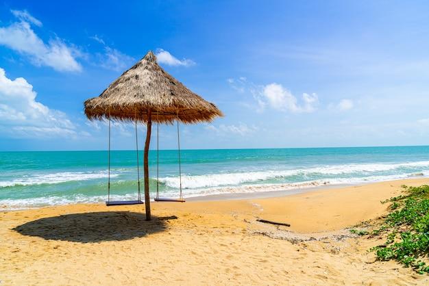 Schommel op strand met oceaan, zee en blauwe lucht