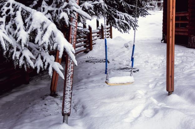 Schommel voor kinderen in de tuin bedekt met sneeuw