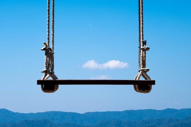 Schommelen op een hoog balkon achter de bergen en heldere luchten drijvende wolken op het inspirerende landschap. droom concept