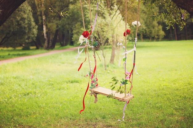 Schommels versierd met linten en bloemen die aan een boom in een zomerpark hangen.