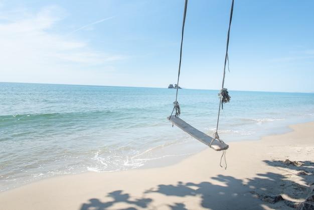 Schommelt op palm tropisch strand, ontspannend in het paradijs.
