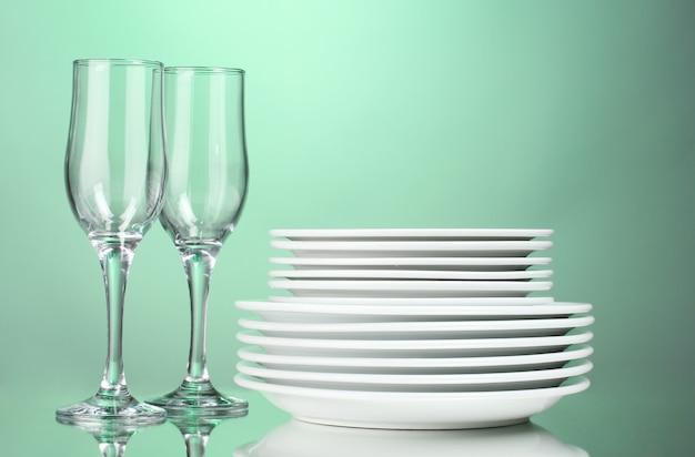 Schone borden en glazen op groene achtergrond