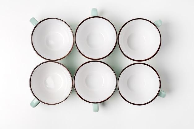 Schone borden, koffie- of theeservies. tal van elegante lege porseleinen bekers, high key, bovenaanzicht en platliggend.