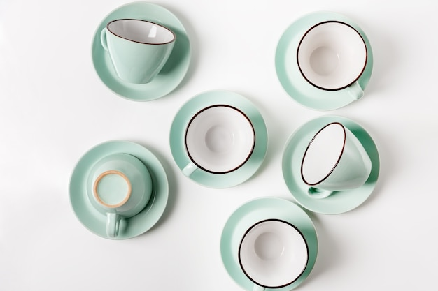 Schone borden, koffie- of theeservies. tal van elegante lichtblauwe porseleinen kop en schotels, high key, bovenaanzicht en platliggend.
