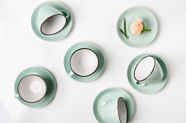 Schone borden, koffie- of theeservies. tal van elegante porseleinen kop en schotels met bloem erin, high key, bovenaanzicht en platliggend.
