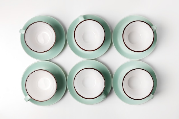 Schone borden, koffie- of theeservies. veel elegante porseleinen kopjes en schotels, high key, bovenaanzicht en platliggend.