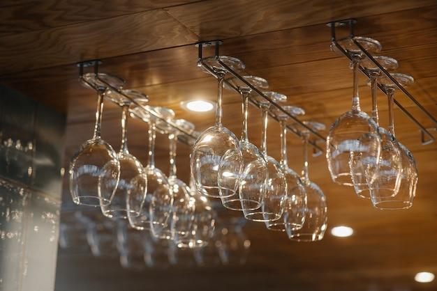 Schone glazen voor alcoholische dranken hangen boven de bar in een modern restaurant