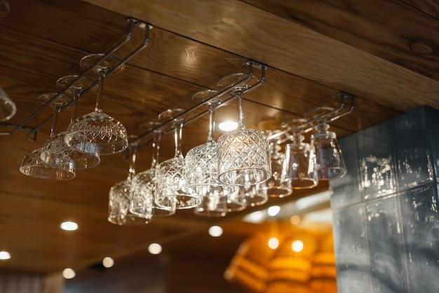 Schone glazen voor alcoholische dranken hangen boven de bar in een modern restaurant.