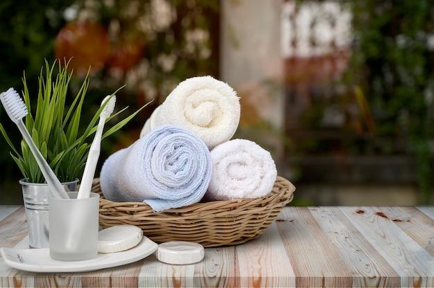 Schone handdoeken in mand met tandenborstel en kamerplant op houten tafel met groene natuur