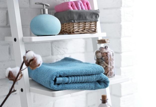 Schone handdoeken met zeepdispenser op planken in de badkamer