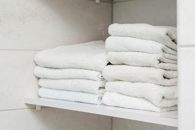 Schone handdoeken op plank in de badkamer. witte handdoeken op de plank. stapel netjes gevouwen witte handdoeken. kast met schoon opgevouwen textiel.