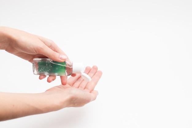 Schone handen en fles met antibacteriële antiseptische gel op witte achtergrond.