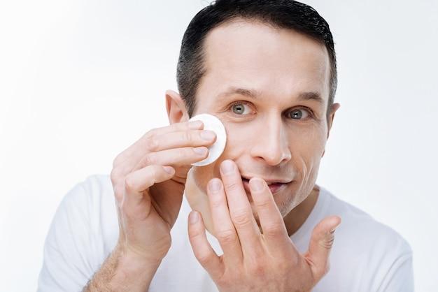 Schone huid. aardige knappe aangename man die een wattenschijfje vasthoudt en zijn huid schoonmaakt terwijl hij erom geeft