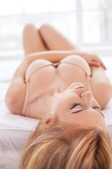 Schone slaapster. aantrekkelijke jonge vrouw in lingerie die in bed ligt en ogen gesloten houdt