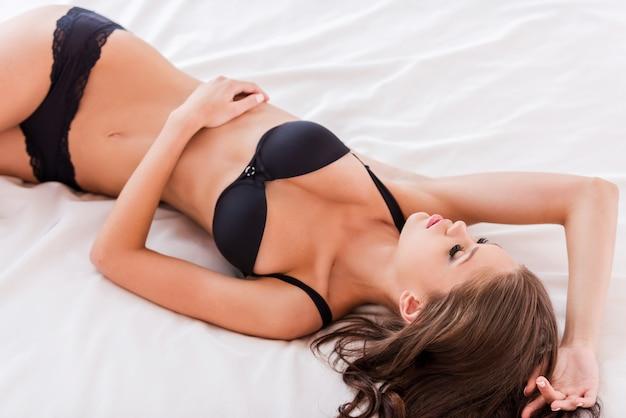 Schone slaapster. bovenaanzicht van mooie jonge bruin haar vrouw in zwarte lingerie in bed liggen en ogen gesloten houden