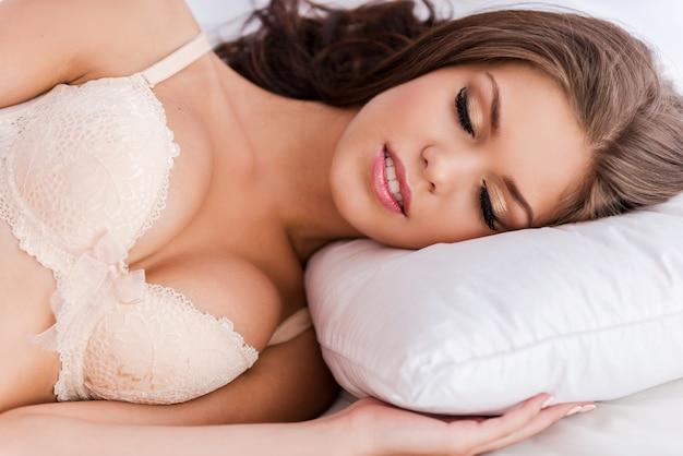 Schone slaapster. mooie jonge bruin haar vrouw in beha liggend in bed en ogen gesloten houden