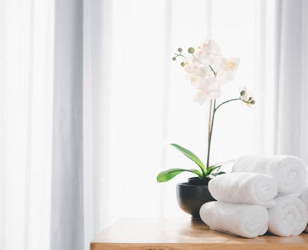 Schone witte handdoeken en prachtige orchideebloemen op houten tafel met wazig witte badkamer achtergrond