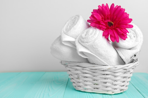 Schone zachte handdoeken met bloem op houten tafel